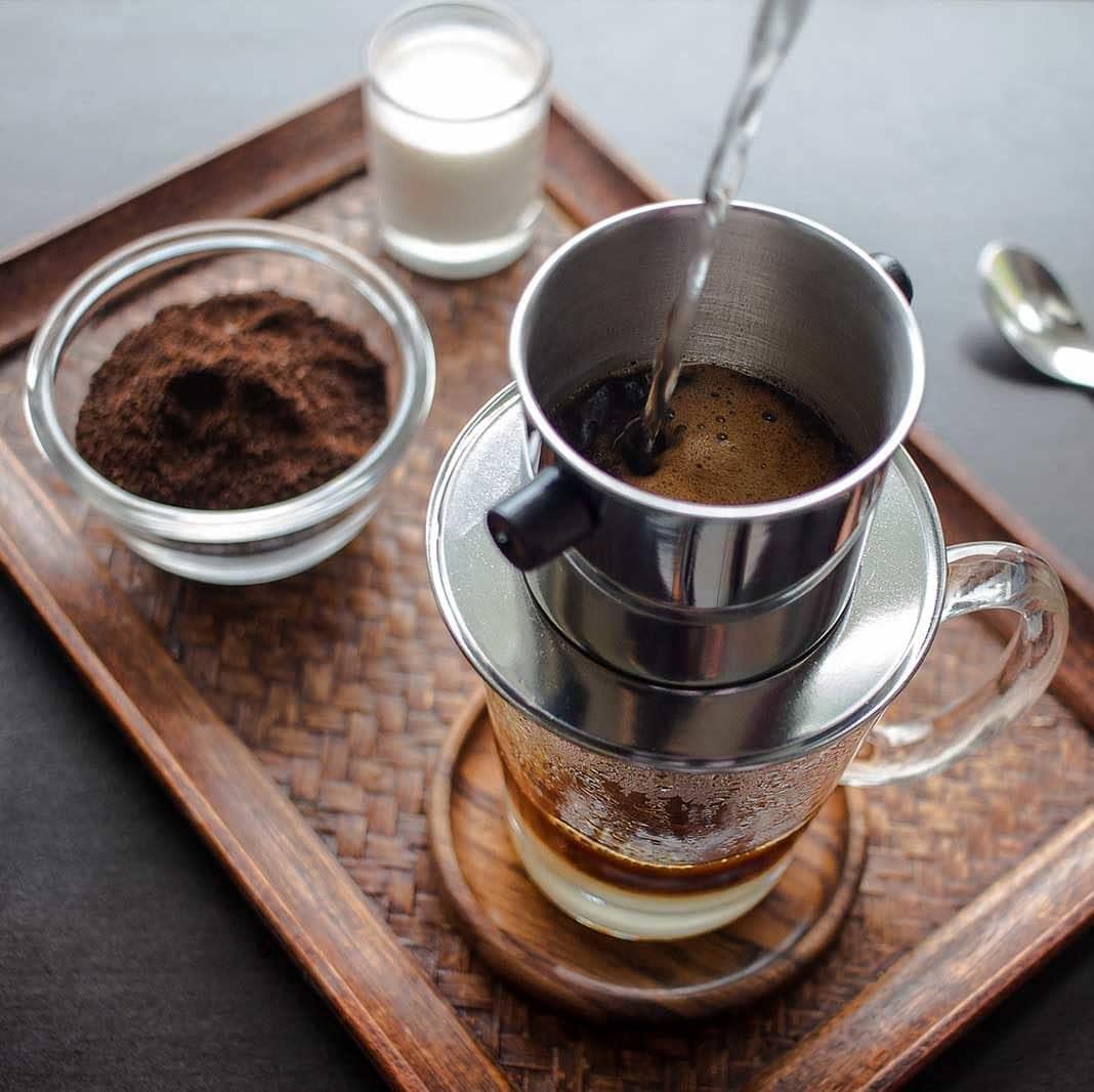 Kaffee-Zubereitung mit einem traditionellen vietnamesischen Kaffeefilter Cafe Phin und gezuckerter Kondensmilch