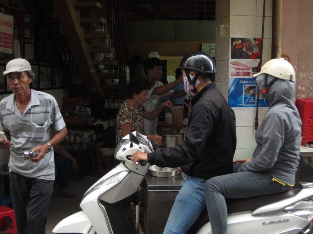 Eine typische Szene im morgendlichen Ho-Chi-Minh-Stadt. Vietnamesen auf dem Weg zur Arbeit warten auf ihren Cà Phê Sữa und Trà Ðá.
